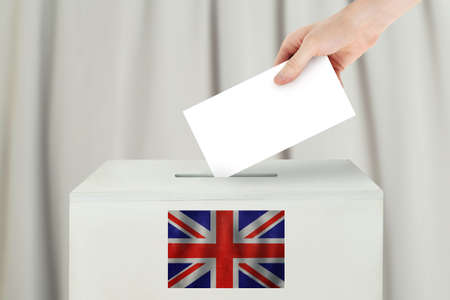 UK Vote concept. Voter hand holding ballot paper for election vote on polling station
