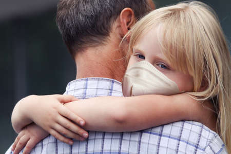 Man carrying child girl in medical face mask