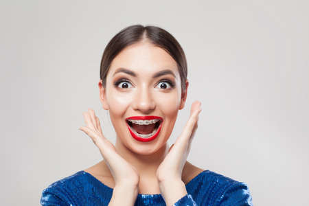 Happy excited woman with braces on teeth on white background