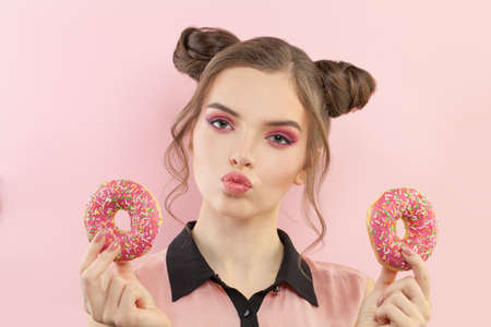 Cute fashion woman eating donut on pastel pink background