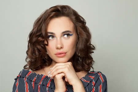 Attractive woman with brown curly bob hairdo looking up aside on white
