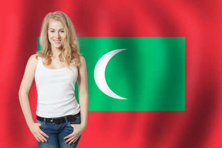 Travel in New Maldives. Happy girl student with New Maldives flag Banco de Imagens
