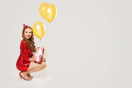 Happy fashion model woman in red dress holding red gift box and yellow balloons on white background 版權商用圖片