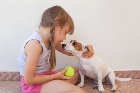Cute child girl and puppy playing with yellow ball together