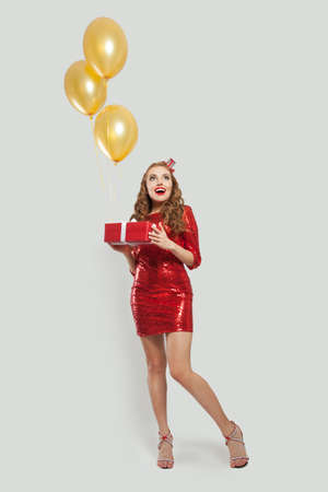 Exsited surprised woman with red gift and yellow balloons standing on white background 版權商用圖片