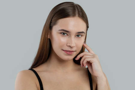 Cute young woman with clear skin and straight hair. Skincare and facial treatment concept