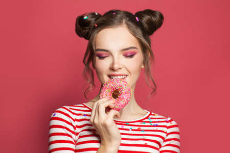 Lovely young woman eating donut