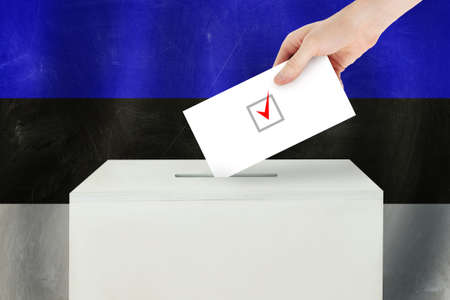 Estonian Vote concept. Voter hand holding ballot paper for election vote on polling station Standard-Bild