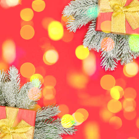 Christmas card composition with golden bokeh light, gifts and Xmas tree branch on red background