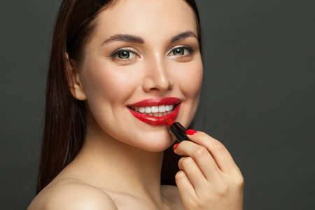 Pretty woman face with red glossy lips and lipstick on black background Standard-Bild