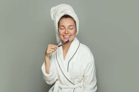Pretty young woman in white bathrobe holding toothbrush with toothpaste Standard-Bild