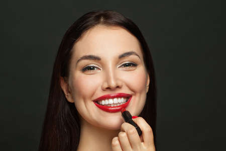 Beautiful woman face with red glossy lips and lipstick on black background Standard-Bild