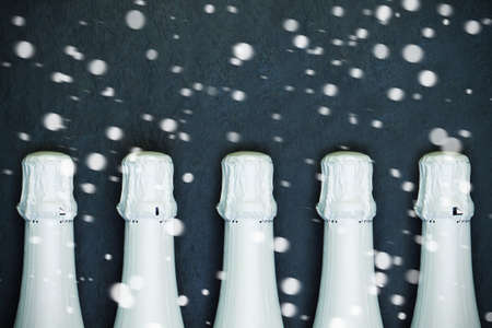 Christmas concept. White Sparkling wine bottles and snow on black background