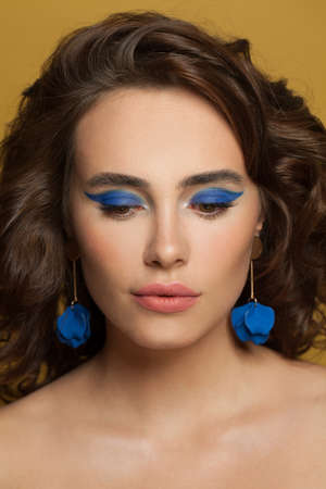 Young brunette model woman with blue eyeshadow makeup and curly hair on yellow background