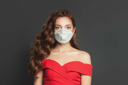 Beautiful woman in protective medical mask on black background