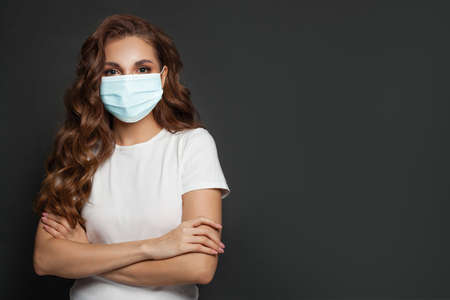 Confident woman wearing protective medical mask and white t-shirt standing with crossed arms on black background Standard-Bild