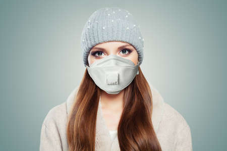 Pretty woman in season clothes and protective medical mask on white