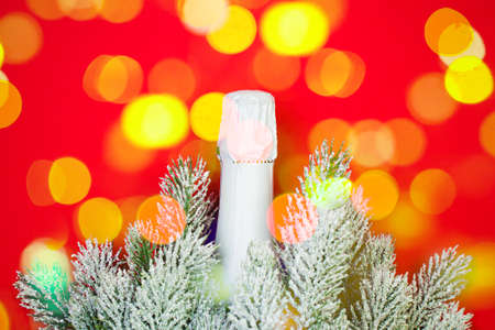 Christmas concept. Colorful Bokeh with Sparkling wine bottle on red background