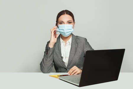 Happy smart business woman in protective medical mask with phone and laptop working in office