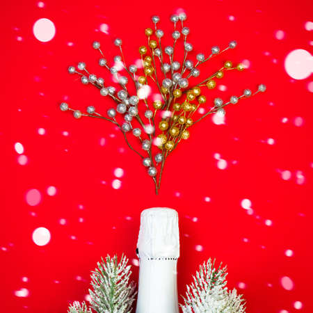 White Sparkling wine bottle on red background with snow and decor, Christmas concept