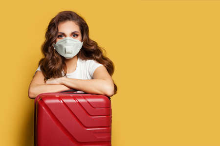 Woman in protective medical mask with suitcase. Travel, weekends and holidays with Covid-19 pandemic concept