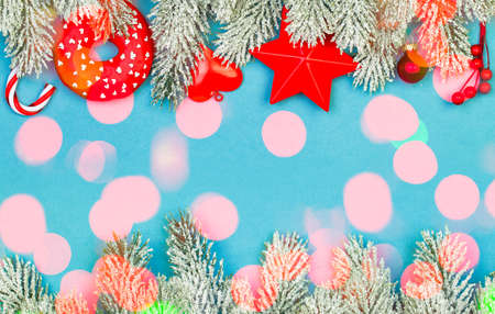 Blue Christmas border composition with colorful bokeh light and red Xmas decorations garland