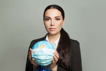 Pretty woman with a globe earth in medical protective mask on gray background