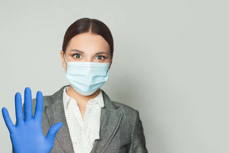 Businesswoman wearing protective face mask and medical gloves with stop gesture
