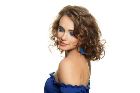 Pretty woman with blue eyeshadow makeup and curly hair isolated on white background