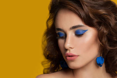 Beautiful woman with blue eyeshadow makeup and curly hair on yellow background Standard-Bild