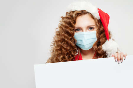 Christmas woman Santa in protective medical mask holding empty singboard card on white
