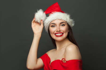 Happy beautiful woman in Santa hat smiling on black. Christmas holiday and New Year party