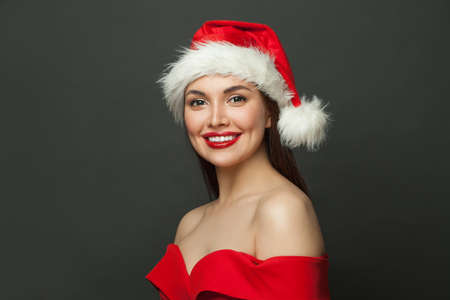 Christmas woman in Santa hat smiling on black background