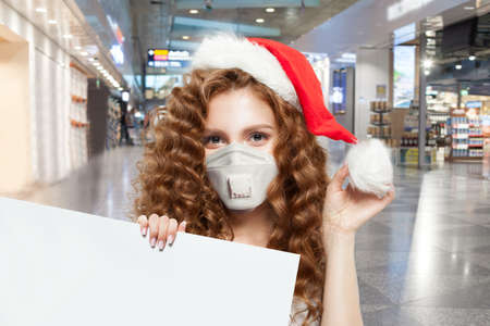 Pretty woman Santa in protective medical mask holding empty signboard in shopping mall. Christmas and New Year sale concept Standard-Bild