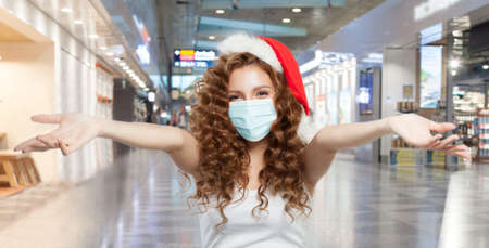 Happy woman Santa in protective medical mask having fun in mall. Open shopping and Christmas sale concept