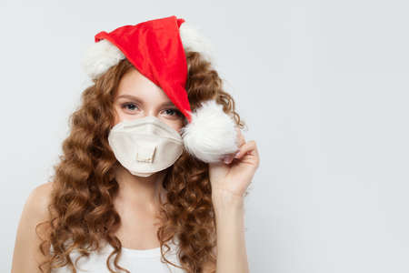 Happy woman in Santa hat and protective medical mask. Christmas and New Year party with Covid-19 pandemic