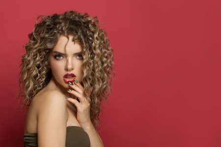 Fashion portrait of perfect young woman with curly hair on red background