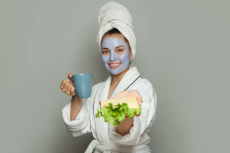 Smiling woman in cosmetic face mask eating breakfast. Facial treatment and skin care concept Banco de Imagens