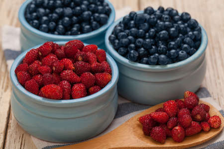 Blueberry and strawberry in ceramic bowls, organic food
