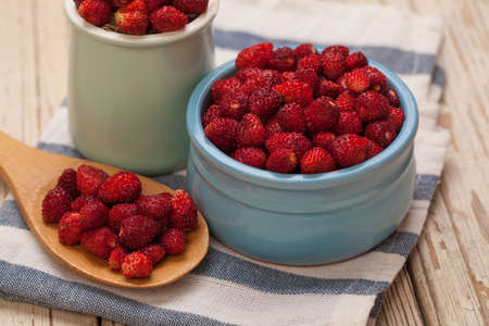 Organic berries red strawberries in ceramic bowl and wooden spoon