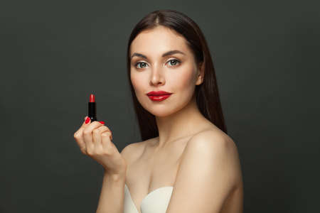 Pretty young brunette woman with red lipstick on black background