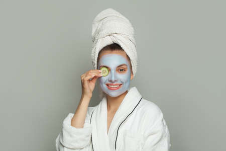 Smiling young woman spa model in moisturizing cosmetic face mask with green cucumber. Facial treatment and skin care concept