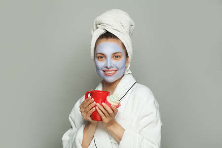 Pretty woman in blue cosmetic face mask eating breakfast and drinking coffee. Female day routine Banco de Imagens