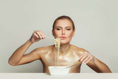 Fashionable woman in gold glitter shimmer eating instant noodles on white background Banco de Imagens