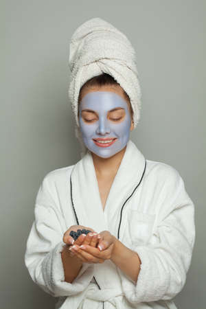 Pretty young woman spa model in blue cosmetic face mask holding organic blueberries. Facial treatment and skin care concept