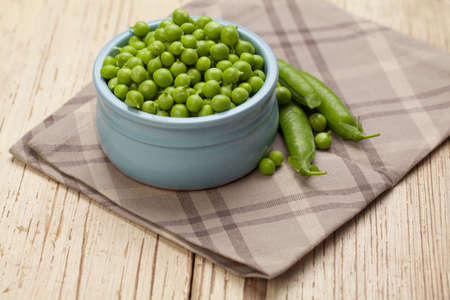Green peas in bowl on gray cotton napkin and wooden background