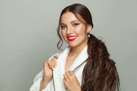 Attractive woman with clear skin and long healthy dark hair on white background. Haircare and facial treatment concept