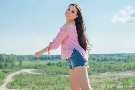 Beautiful smiling woman in summer day against blue sky outdoors