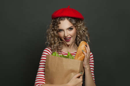 Happy french woman in red beret on black wall background