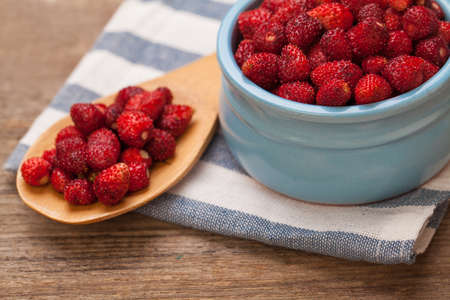 Red strawberries in blue bowl and brown wooden spoon